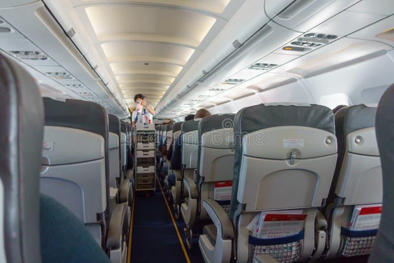 Stewardess bietet Lebensmittel an und trinkt zu den Touristenklassepassagieren lizenzfreie stockfotos