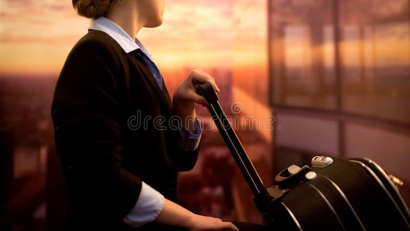 Stewardess die met bagage in luchthaven, het bewonderen zonsopgang wachten, zakenreis royalty-vrije stock afbeelding