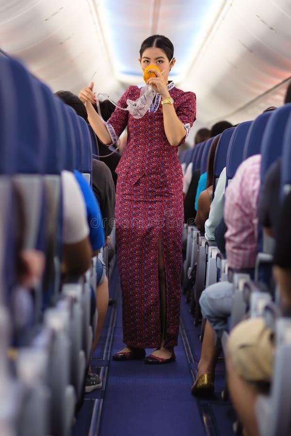 Stewardess, die Sauerstoffmaske zeigt stockfoto