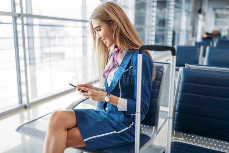 Stewardess die telefoon op wachtend gebied in luchthaven met behulp van stock foto's