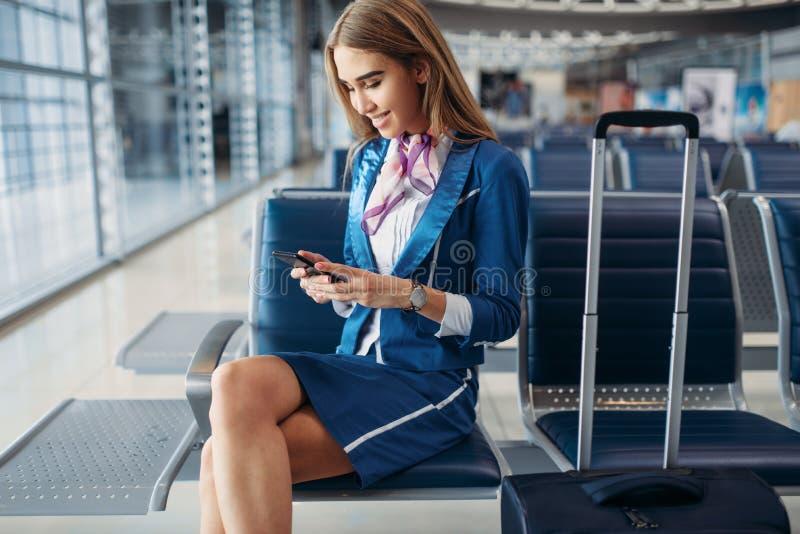 Stewardess die telefoon op wachtend gebied in luchthaven met behulp van stock foto