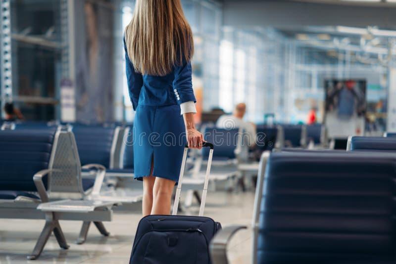 Stewardess, die zwischen Sitzreihen im Flughafen geht lizenzfreie stockfotos