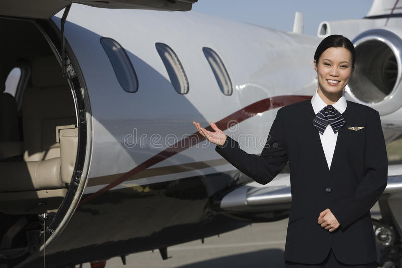 Download Stewardess Gesturing At Airfield Stock Photo - Image: 29653204