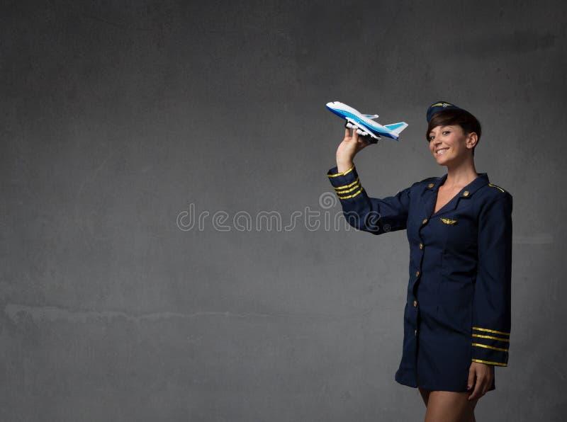 Stewardess het plaing met een stuk speelgoed vliegtuig stock afbeelding