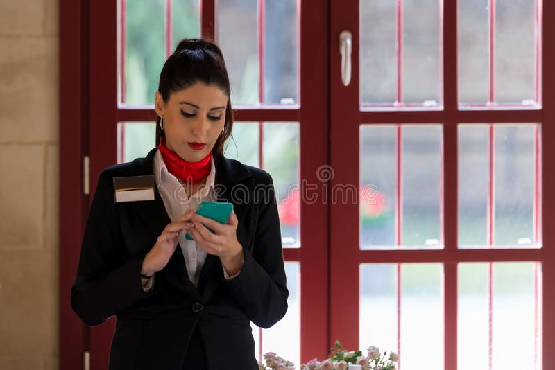 Stewardess looking for information on her mobile phone stock photo