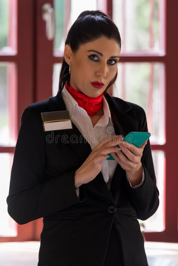 Stewardess looking for information on her mobile phone royalty free stock photography
