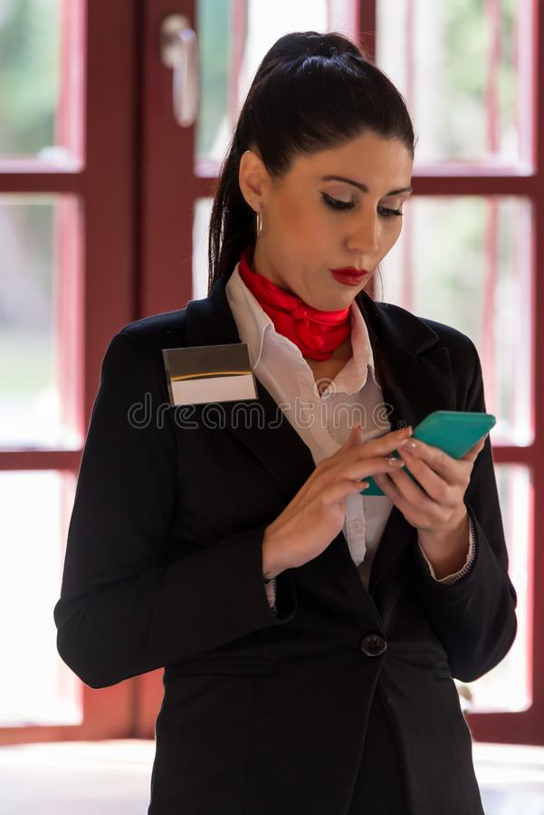 Stewardess looking for information on her mobile phone stock photography