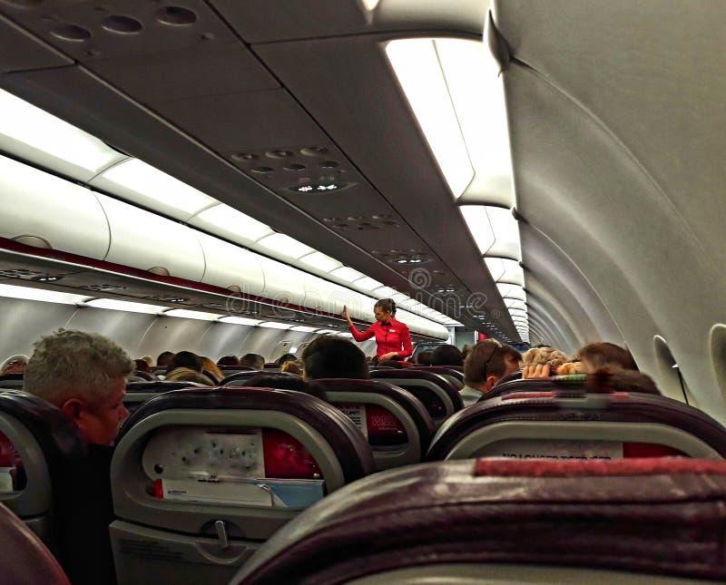 Stewardess on the plane, telling safety. stock photo