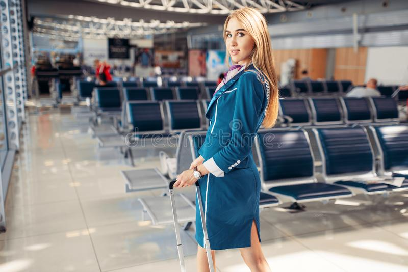 Stewardess with suitcase in airport waiting room stock image