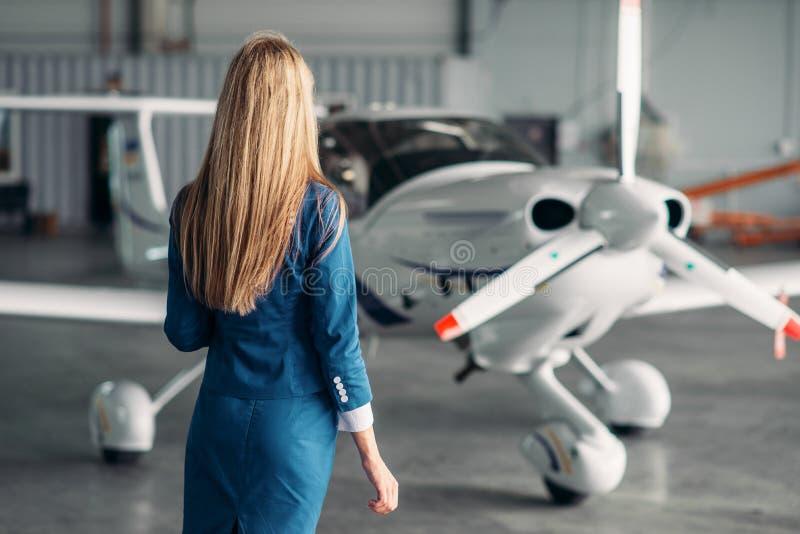 Stewardess tegen schroefturbinevliegtuig in hangaar stock afbeelding