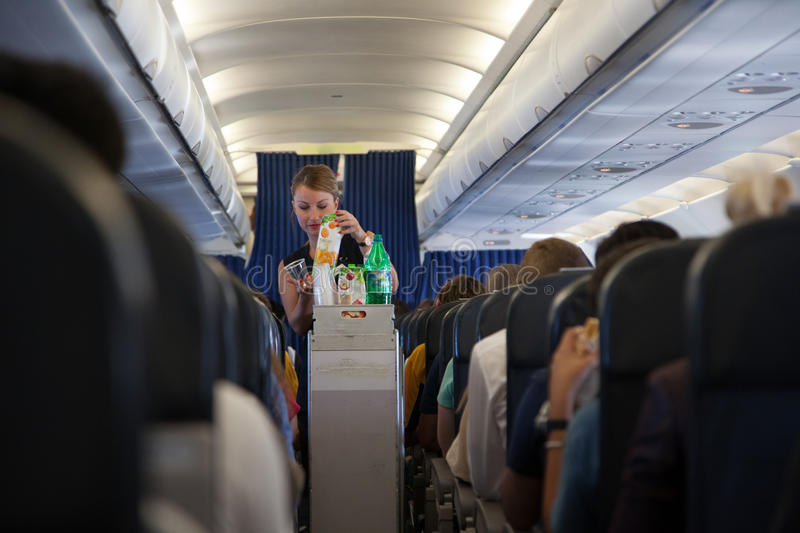 A stewardess works on the airplane royalty free stock photography