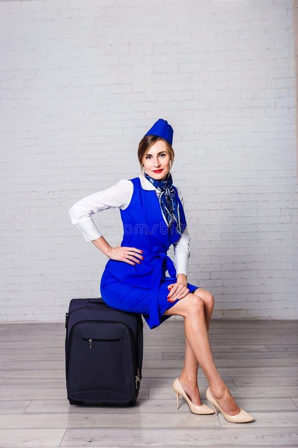Stewardessen sitter på en resväska royaltyfri fotografi