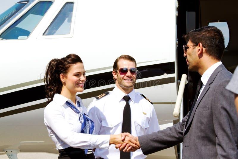 Stewardesy i pilota powitania pasażer obraz stock