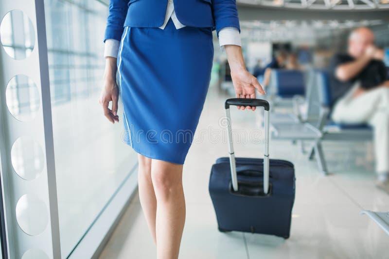 Stewardesy walizka w lotniskowej sala i nogi zdjęcia stock