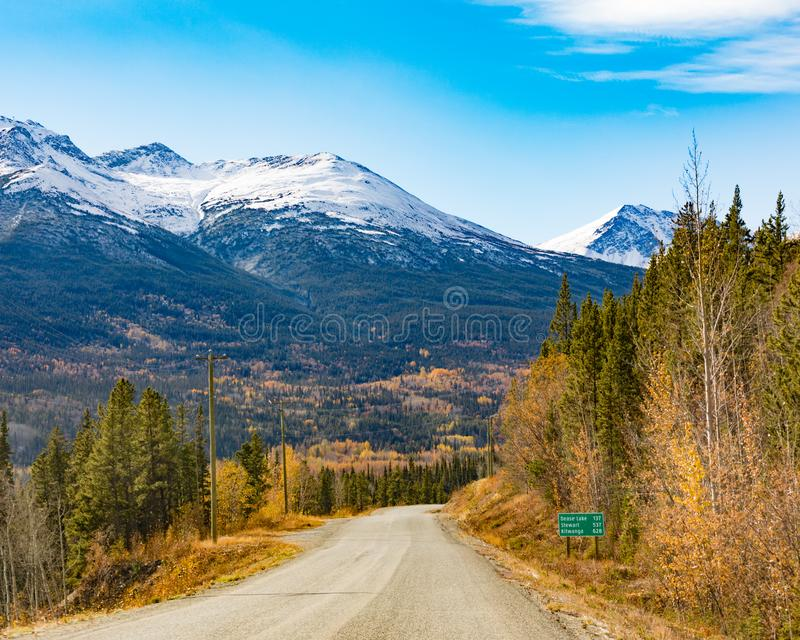 Stewart-Cassiar Highway 37 in fall BC Canada. Late autumn fall and snowy mountains 137 km from Dease Lake on Stewart-Cassiar Highway 37 in Northern British stock image