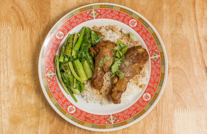 Stewed chicken or Braised chicken with Chinese kale and rice in dish on wooden table. Stewed chicken or Braised chicken with Chinese kale and rice in dish stock photos