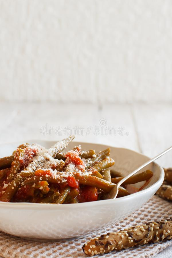 Stewed french bean with tomato. And grated cheese stock photography