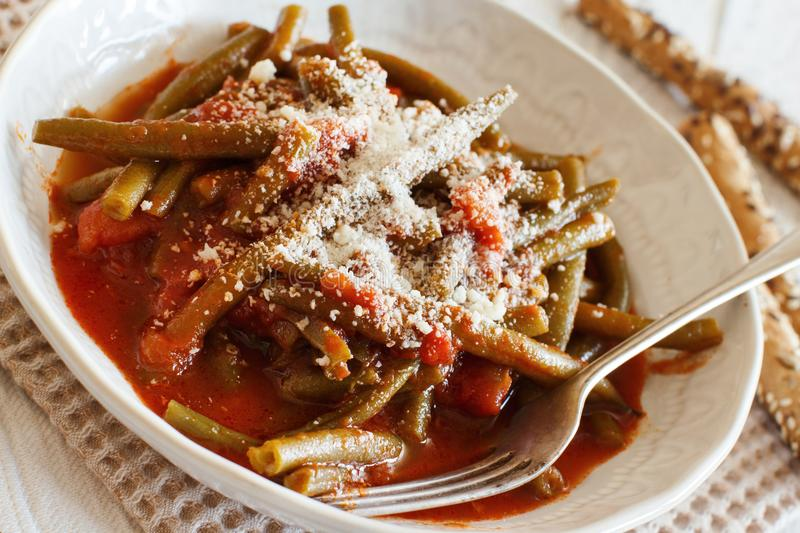 Stewed french bean with tomato. And grated cheese stock image