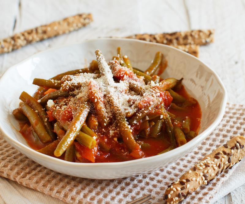 Stewed french bean with tomato. And grated cheese stock photo