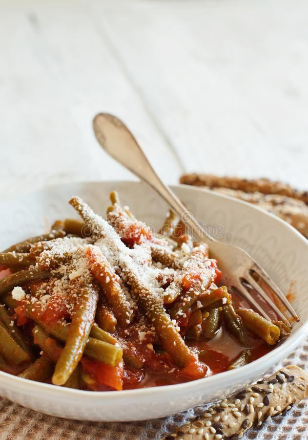 Stewed french bean with tomato. And grated cheese royalty free stock image