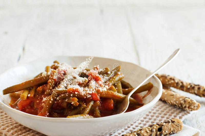 Stewed french bean with tomato. And grated cheese royalty free stock images