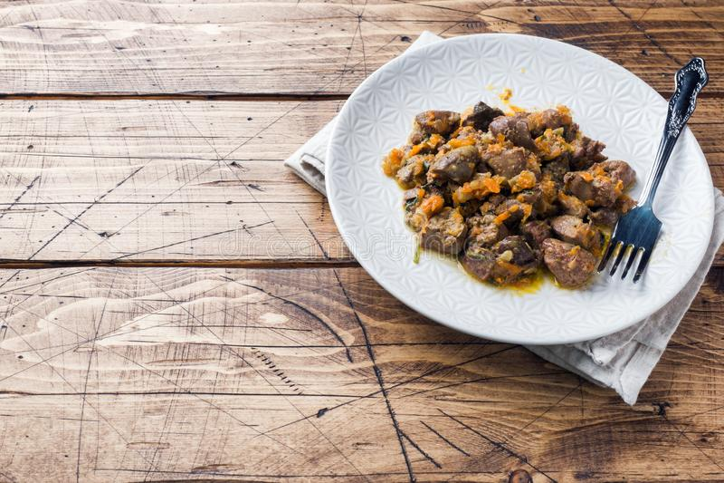 Stewed kurczak wątróbka z warzywami na talerzu Drewniany tło fotografia stock