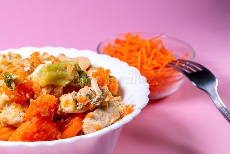 Stewed kurczak z warzywami, marchewki, kapusta na talerzu obok rusztowych świeżych marchewek Różowy tło obrazy stock