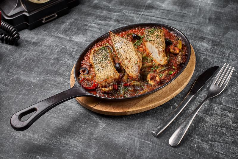 Stewed perch in tomato sauce, serve food in the Provencal style, in a pan. top view , copy Space. stock photos