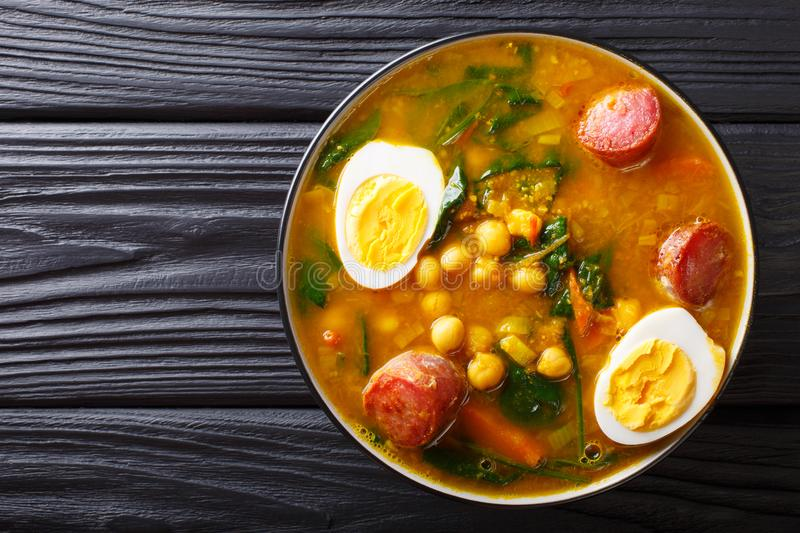 Stewed Potaje de garbanzos chickpeas, spinach, chorizo sausages, boiled eggs close-up in a bowl. horizontal top view. Stewed Potaje de garbanzos chickpeas royalty free stock photo