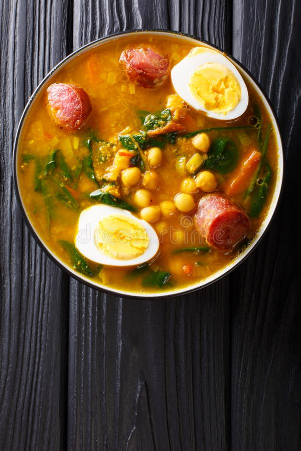 Stewed Potaje de garbanzos chickpeas, spinach, chorizo sausages, boiled eggs close-up in a bowl. Vertical top view. Stewed Potaje de garbanzos chickpeas, spinach royalty free stock image