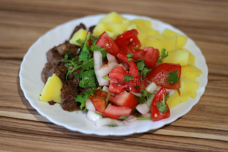 Stewed potatoes with fried beef, onions and red tomatoes with greens on a gravy stock images