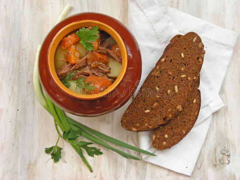 Stewed rabbit with vegetables Goulash in Copper Pot on Wooden Surface, roasted beef meat with carrot, leek, onion in round ceramic. Stewed rabbit with Goulash in stock photos