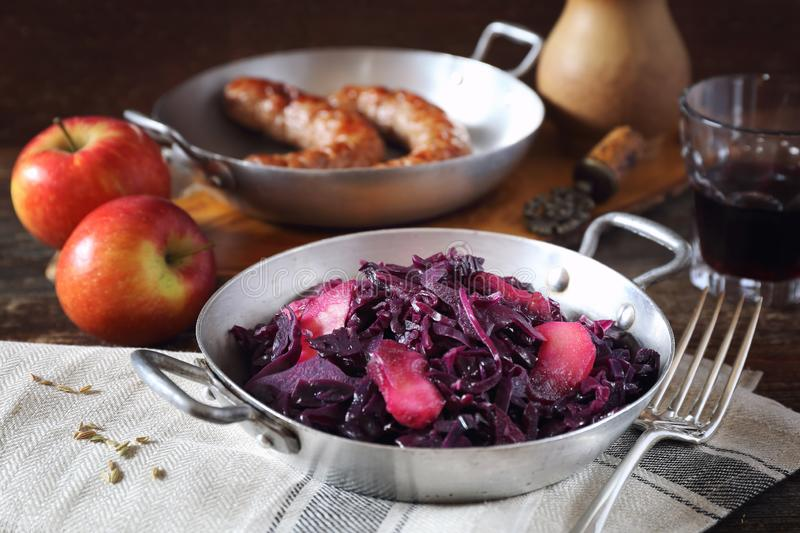 Stewed red cabbage with spices and apples. Garnish for fried sausages. Wooden background, rustic style stock photos