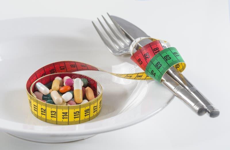 Stia il concetto a dieta il nastro di misurazione ha avvolto le compresse di Twith su un piatto fotografia stock