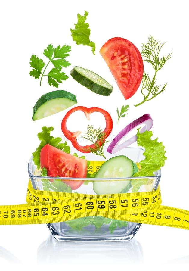 Stia il concetto a dieta Ortaggi freschi che cadono nella ciotola di vetro immagine stock