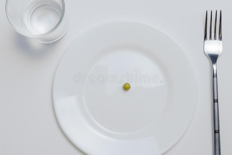 Stia il concetto a dieta un pisello su un piatto bianco vuoto con la forcella fotografie stock libere da diritti