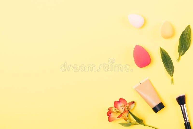 Stichting in buis naast hulpmiddelen voor professionele make-up: de synthetische borstel en het mengen sponsen, vlakte leggen sam royalty-vrije stock foto's