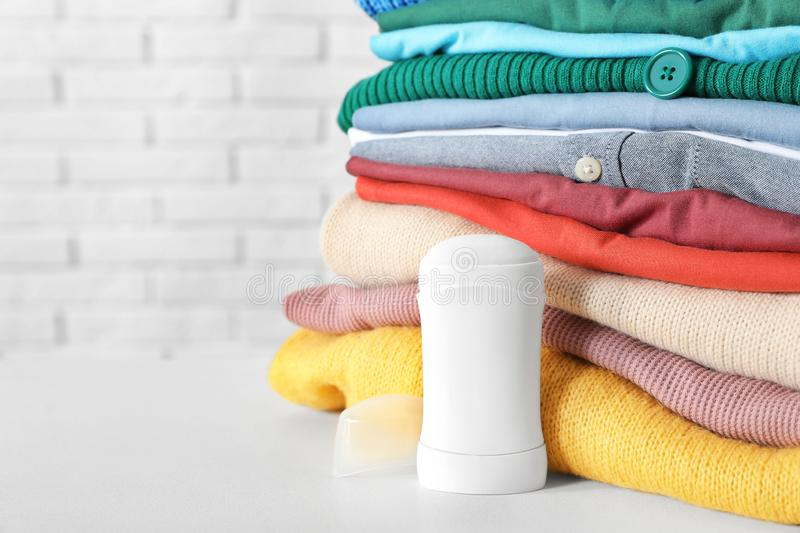 Stick deodorant near clean clothes on white table. Space for text stock photos