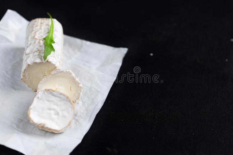 Stick of a goat cheese on black stone background. Fresh goat che. Ese with copy space, cut in pieces royalty free stock photos