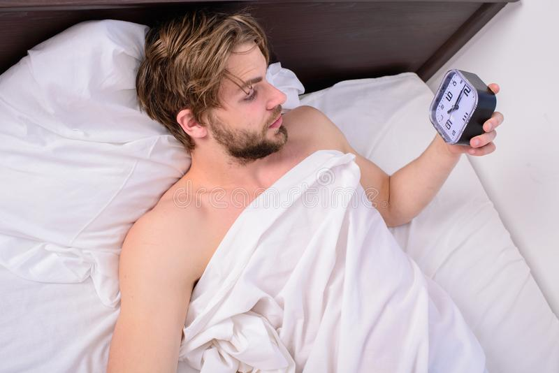 Stick sleep schedule same bedtime and wake up time. Man sleepy drowsy unshaven bearded face covered with blanket having royalty free stock photos