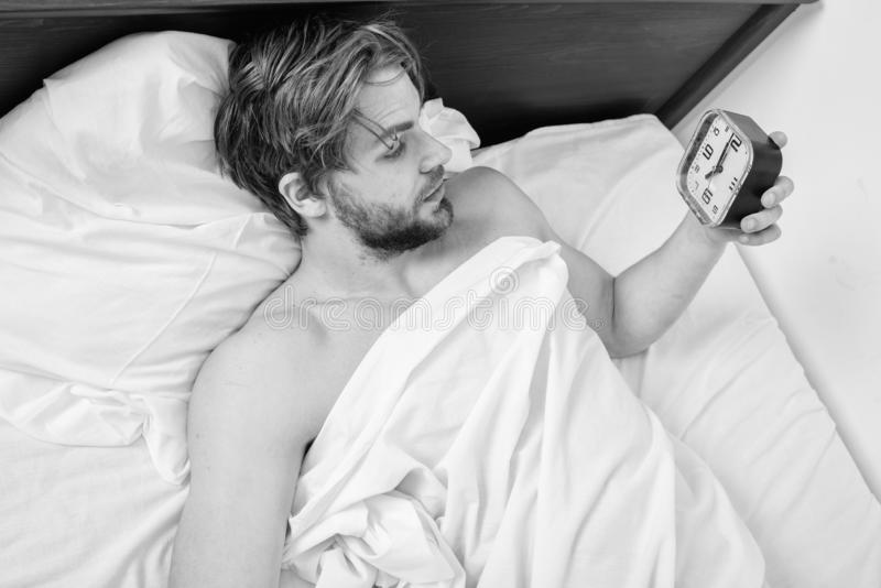 Stick sleep schedule same bedtime and wake up time. Man sleepy drowsy unshaven bearded face covered with blanket having royalty free stock image