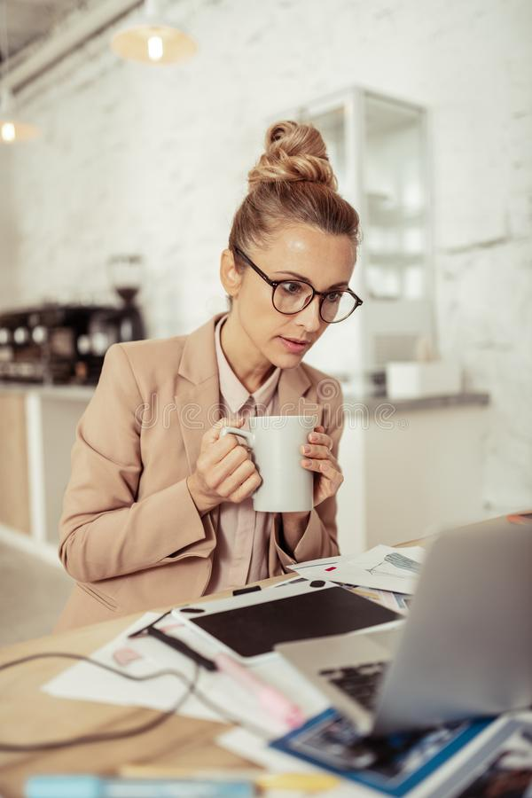 Concentrated woman drinking coffee and looking at her laptop. royalty free stock photography