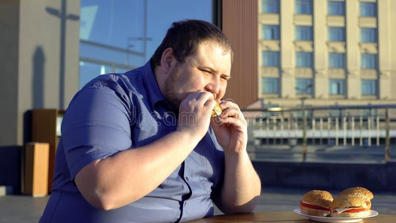 Stickande snabbmathamburgare för fet man, matställe på det utomhus- kafét som äter för mycket problem royaltyfria foton