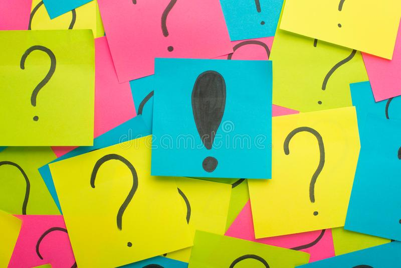 sticker with exclamation mark. Around it are glued a lot with question marks. Beautiful picture from above. Concept, a question of stock image