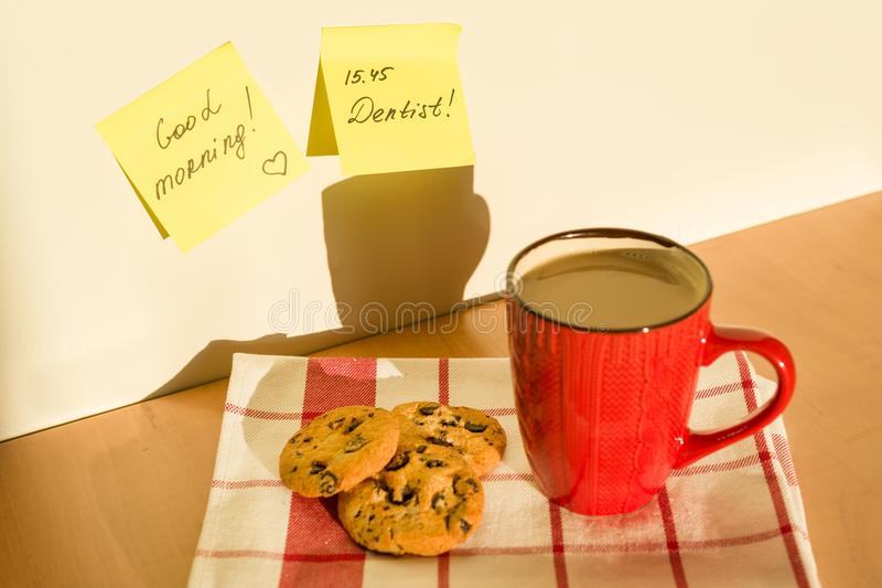 Sticker GOOD MORNING, DENTIST on the table at home. Background - tablecloth with cup of coffee and cookies. Sticker GOOD MORNING, DENTIST on the table at home stock photos