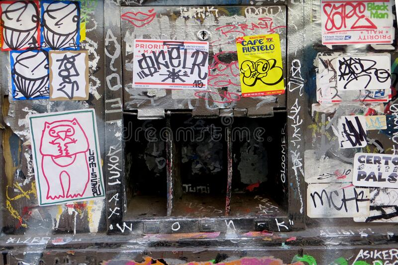 sticker-and-graffiti-covered wall with openings stock photo