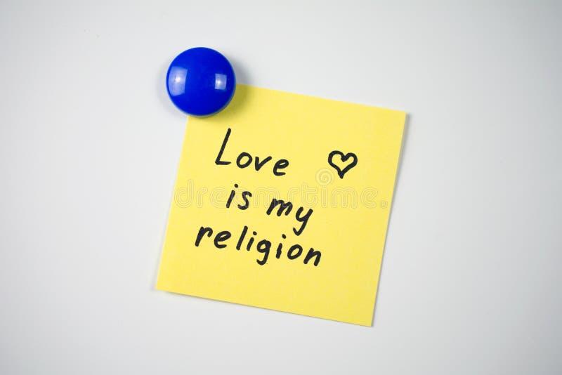 Sticker Love is my religion. Yellow sticker inscription Love is my religion attached  blue magnet  white fridge. close-up stock photography