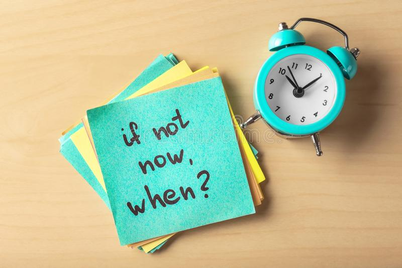 Sticker with phrase If not now, when? and alarm clock on table. Time management concept stock photo