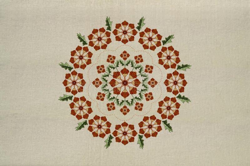 Stickerei der runden Verzierung der orange Blumen auf verdrehten Stämmen mit Blättern auf Baumwollgewebe stock abbildung