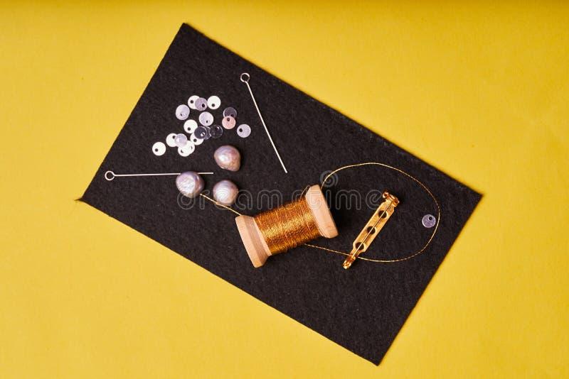 Stickereiprodukte und -werkzeuge Spulenmetallfaden, Perlen und ein Stift mit der Nadel auf dem schwarzen Filz stockbilder